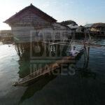 Seorang bapak suku Bajo mendayung perahunya di antara rumah-rumah yang berdiri menjorok ke laut di Pulau Kabalutan, Kepulauan Togean, Tojo Unauna, Sualwesi tengah. ANTARAFOTO/Basri Marzuki/18