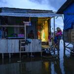 Warga beraktivitas di rumahnya yang digenangi banjir rob atau air pasang laut di Desa Tompe, Kecamatan Sirenja, Kabupaten Donngala, Sulawesi Tengah, Minggu (12/1/2020).