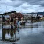 Sejumlah warga duduk di sebuah Pos Kamling di tengah genangan banjir rob atau air pasang laut di Desa Tompe, Kecamatan Sirenja, Kabupaten Donngala, Sulawesi Tengah, Minggu (12/1/2020).