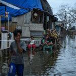 Warga beraktivitas di depan rumahnya yang digenangi banjir rob atau air pasang laut di Desa Tompe, Kecamatan Sirenja, Kabupaten Donngala, Sulawesi Tengah, Minggu (12/1/2020).